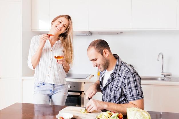 Junge frau, die in der hand weinglas betrachtet ihren ehemann betrachtet das gemüse in der küche hält Kostenlose Fotos