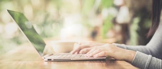Junge frau, die in der kaffeestube am holztisch sitzt, kaffee trinkt und laptop verwendet. Premium Fotos