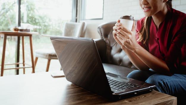 Junge frau, die in der kaffeestube mit dem halten der heißen kaffeepapierschale sitzt. Premium Fotos