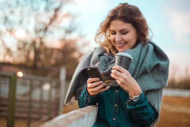 Junge frau, die in einem park mit einem großen mitnehmerkaffee und einem handy sich entspannt. Premium Fotos