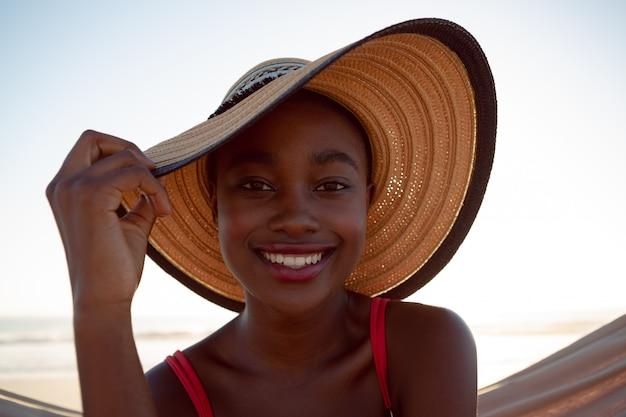 Junge frau, die in einer hängematte auf dem strand sich entspannt Kostenlose Fotos