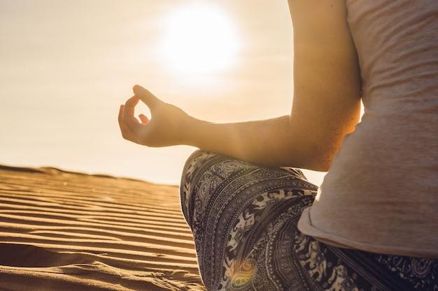 Junge frau, die in rad sandiger wüste bei sonnenuntergang oder im morgengrauen meditiert Premium Fotos
