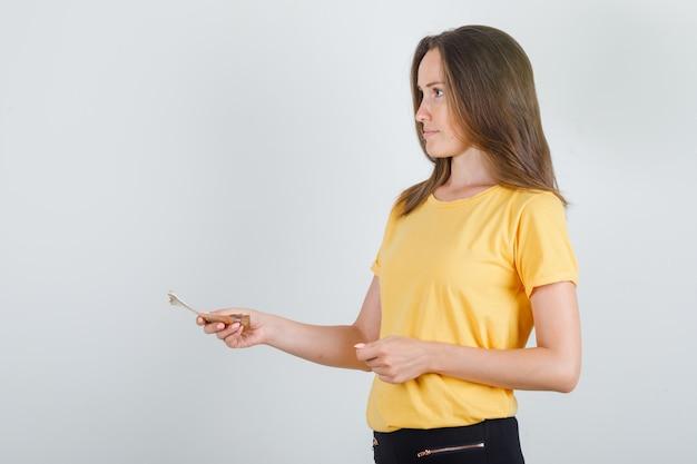 Junge frau, die jemand geld im gelben t-shirt zahlt Kostenlose Fotos