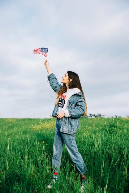 Junge frau, die kleine amerikanische flagge im arm betrachtet Kostenlose Fotos