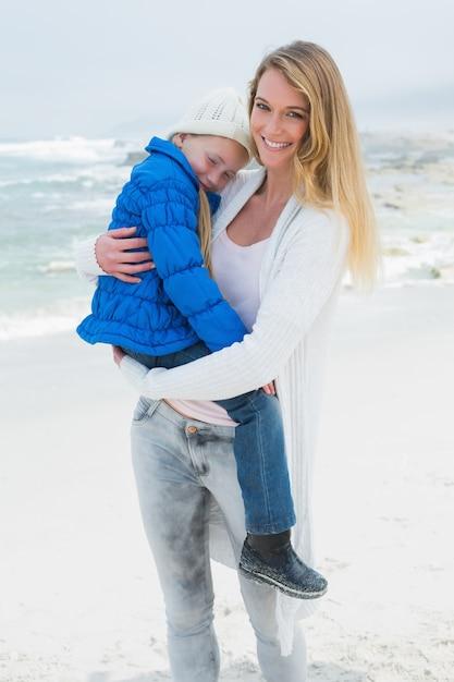 Junge frau, die kleines mädchen am strand trägt | Premium-Foto
