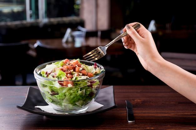 Junge frau, die köstlichen thunfischsalat in einem ausgefallenen restaurant isst, kalorienarme nahrhafte mahlzeit - vegetarisch Premium Fotos