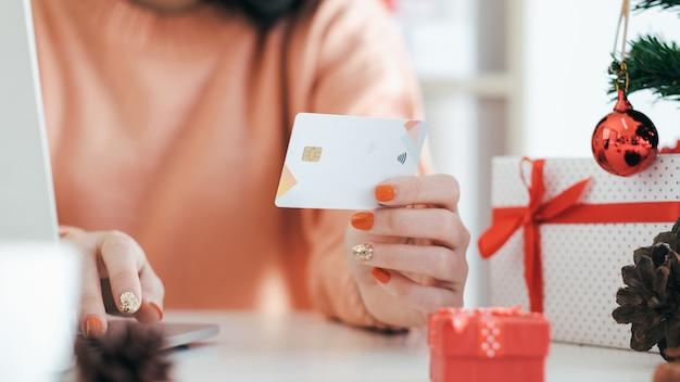 Junge frau, die kreditkarte hält und online kaufen tut. Premium Fotos