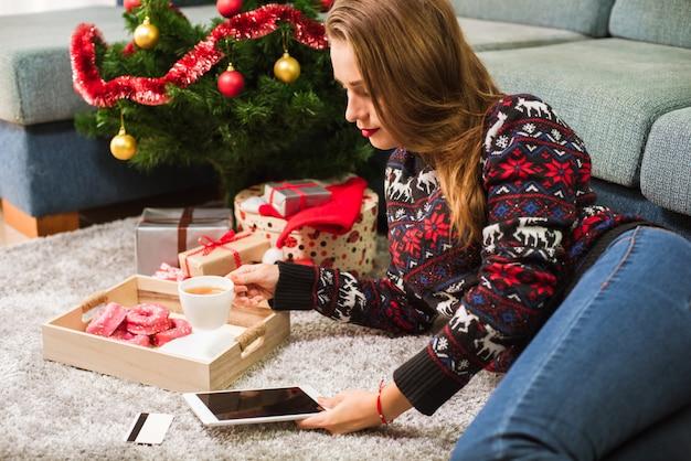 Junge frau, die kreditkarte und tablette auf weihnachten hält Premium Fotos