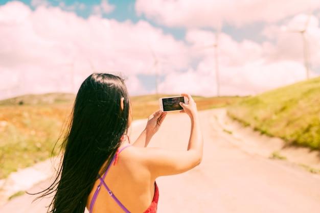Junge frau, die landschaft am telefon fotografiert Kostenlose Fotos
