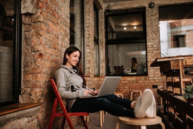 Junge frau, die laptop beim hören von musik auf kopfhörern verwendet. backsteinmauer im hintergrund. Premium Fotos