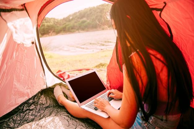 Junge frau, die laptop im zelt verwendet Kostenlose Fotos