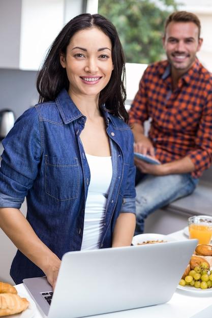 Junge frau, die laptop verwendet und mann, der digitale tablette verwendet Premium Fotos