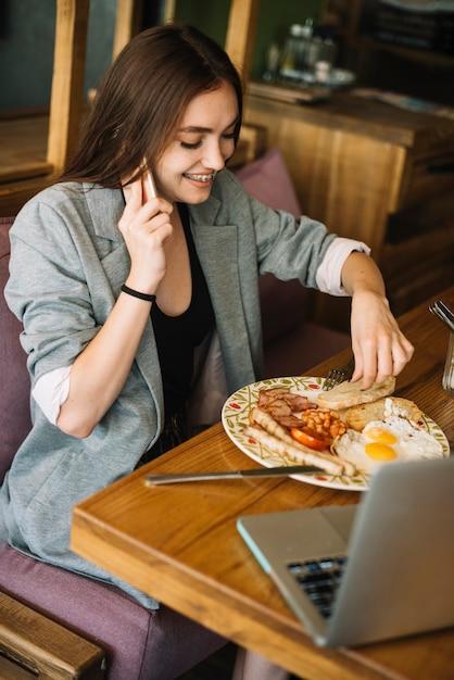Junge frau, die lebensmittel im restaurant spricht am handy isst Kostenlose Fotos