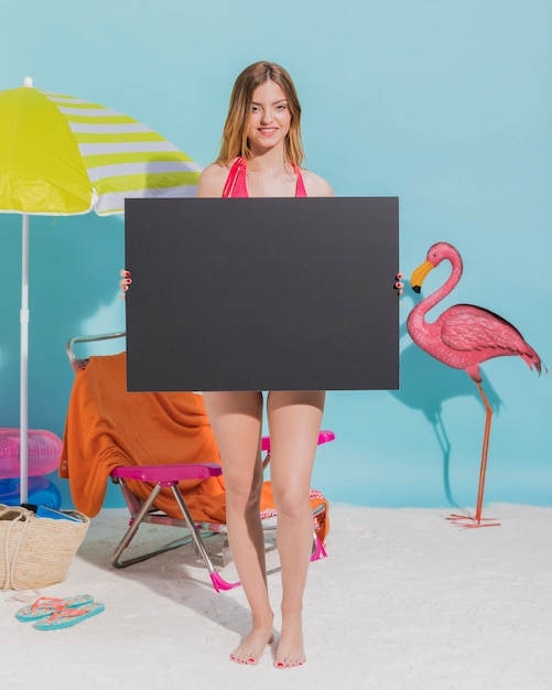 Junge frau, die leeres dunkles blatt papier hält Kostenlose Fotos