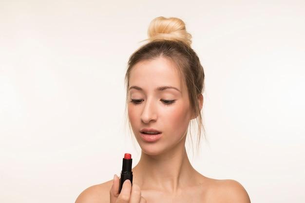 Junge frau, die lippenstift betrachtet Kostenlose Fotos