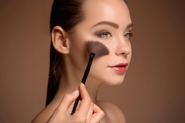 Junge frau, die make-up auflegt Kostenlose Fotos