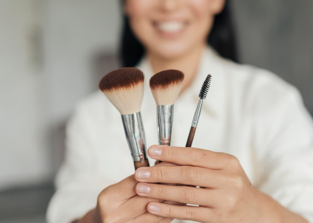 Junge frau, die make-up-bürsten hält Premium Fotos