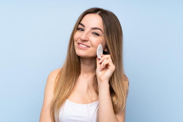 Junge frau, die make-up von ihrem gesicht mit baumwollauflage entfernt Premium Fotos