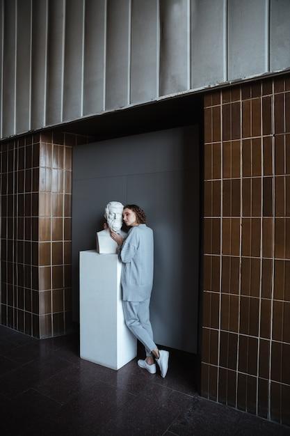 Junge frau, die marmorbüste berührt Kostenlose Fotos