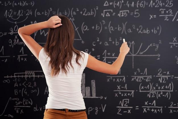 Junge frau, die matheproblem auf tafel betrachtet Kostenlose Fotos