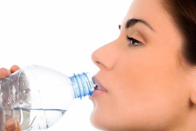 Junge frau, die mineralwasserflasche trinkt, Kostenlose Fotos