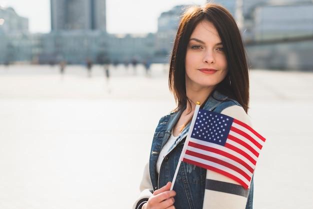 Junge frau, die mit amerikanischer flagge während des unabhängigkeitstags aufwirft Kostenlose Fotos