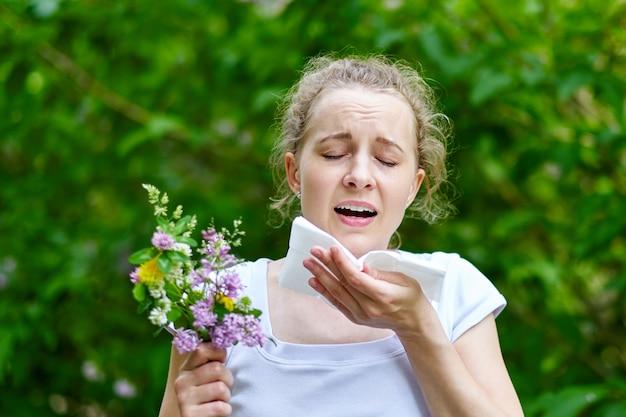 Junge frau, die mit blumenstrauß von blumen niest. konzept: saisonale allergie. Premium Fotos