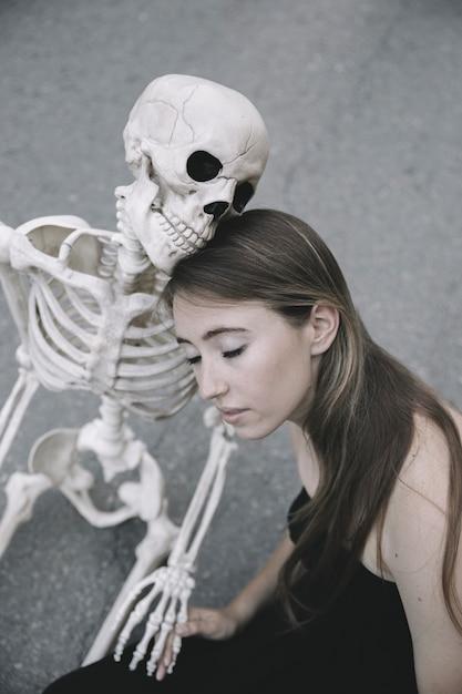 Junge frau, die mit dem skelett sitzt und seine hand hält Kostenlose Fotos
