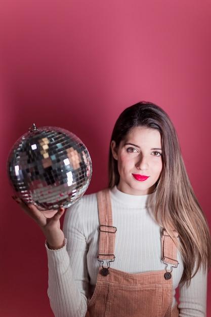 Junge frau, die mit discokugel steht Kostenlose Fotos