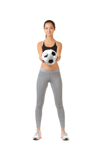 Junge frau, die mit einem fußball spielt Premium Fotos