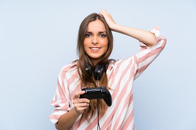 Junge frau, die mit einem videospielcontroller über lokalisierter blauer wand spielt Premium Fotos