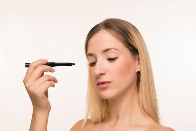 Junge frau, die mit eyeliner in richtung zu ihrem gesicht zeigt Kostenlose Fotos