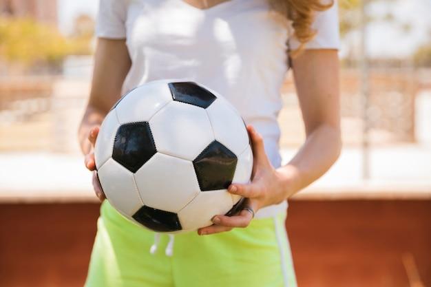 Junge frau, die mit fußball steht Kostenlose Fotos