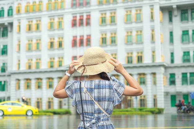 Junge frau, die mit hut, glücklicher asiatischer reisenderbesuch am bunten gebäude des regenbogens in clarke quay, singapur reist. wahrzeichen und beliebt für touristische attraktionen. asien-reisekonzept Premium Fotos