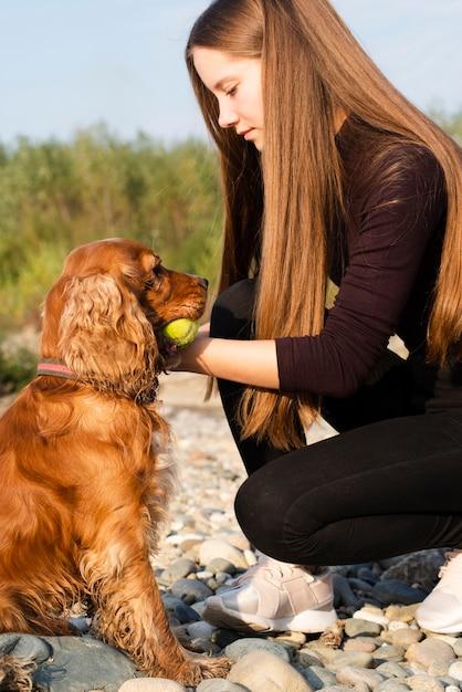 Junge frau, die mit ihrem hund spielt | Kostenlose Foto