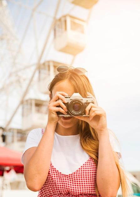 Junge frau, die mit kamera am vergnügungspark fotografiert Kostenlose Fotos