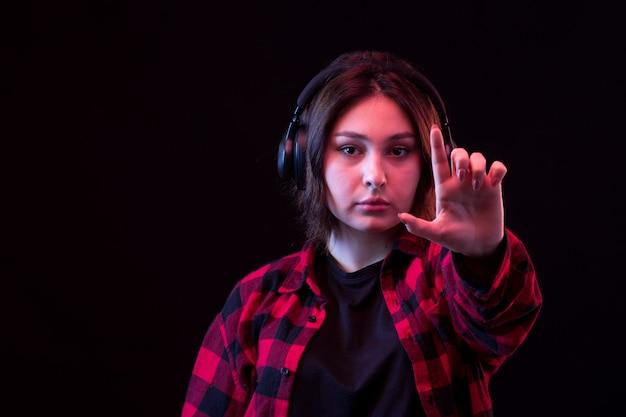 Junge frau, die mit kariertem rotem und schwarzem hemd unter verwendung der kopfhörer aufwirft Kostenlose Fotos