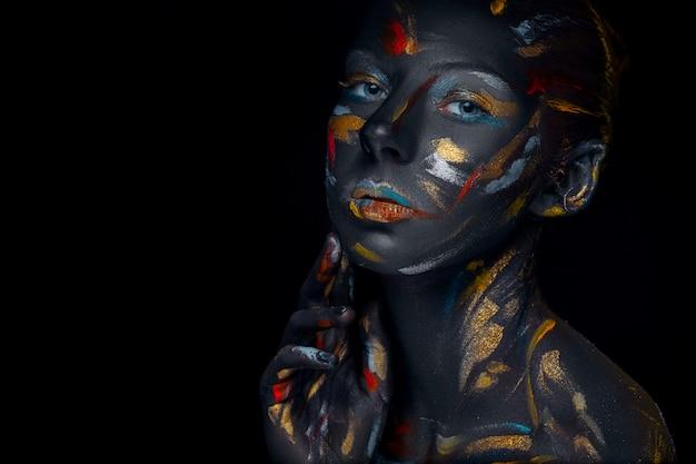 Junge frau, die mit schwarzer farbe bedeckt aufwirft Kostenlose Fotos