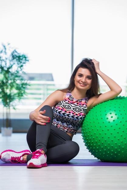 Junge frau, die mit schweizer ball im gesundheitskonzept trainiert Premium Fotos