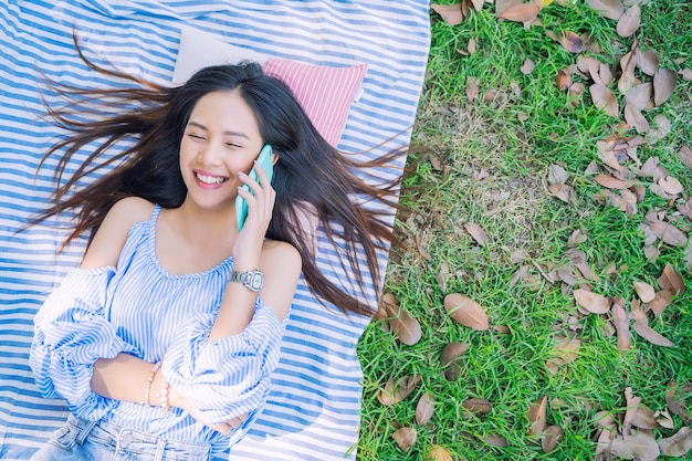 Junge frau, die mit smartphone auf dem boden im garten mit glücklichem nennt Premium Fotos