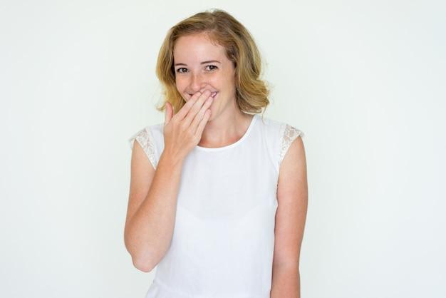 Junge frau, die mund mit der hand lacht und bedeckt Kostenlose Fotos