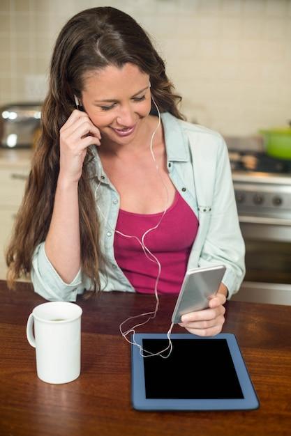 Junge frau, die musik auf smartphone mit tablette und kaffeetasse auf küchenarbeitsplatte hört Premium Fotos