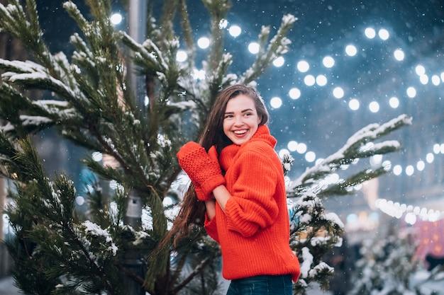 Junge frau, die nahe dem weihnachtsbaum auf der straße aufwirft Kostenlose Fotos