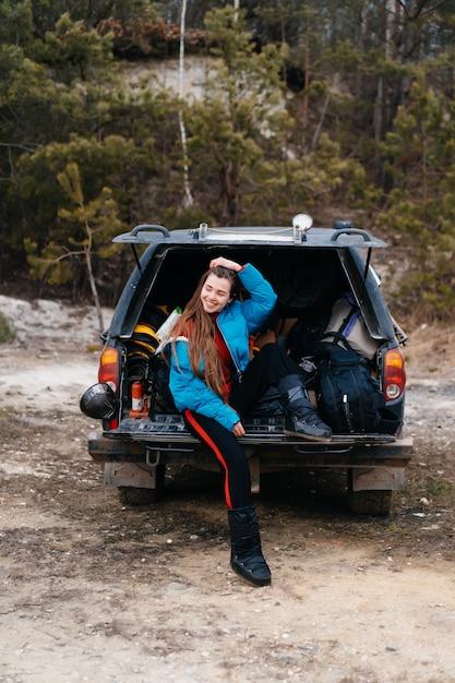 Junge frau, die natur beim sitzen im autokofferraum genießt Kostenlose Fotos