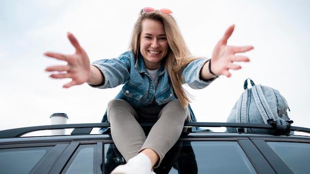 Junge frau, die oben auf dem auto sitzt Kostenlose Fotos