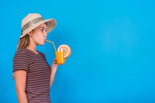 Junge frau, die orangensaft auf blauem hintergrund trinkt Kostenlose Fotos