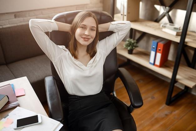 Junge frau, die pause während des arbeitstages hat. sie hält die hände hinter dem kopf und lächelt. sie sitzt im zimmer. Premium Fotos