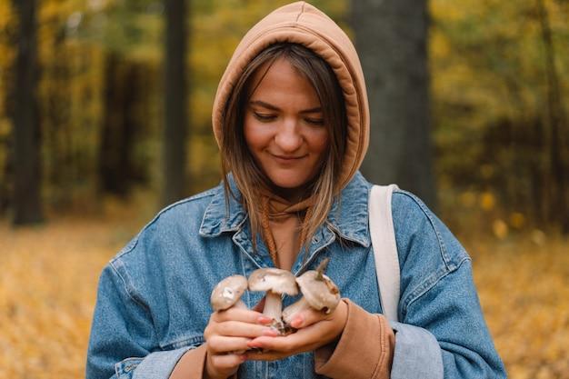 Junge frau, die pilze im wald hält. Premium Fotos