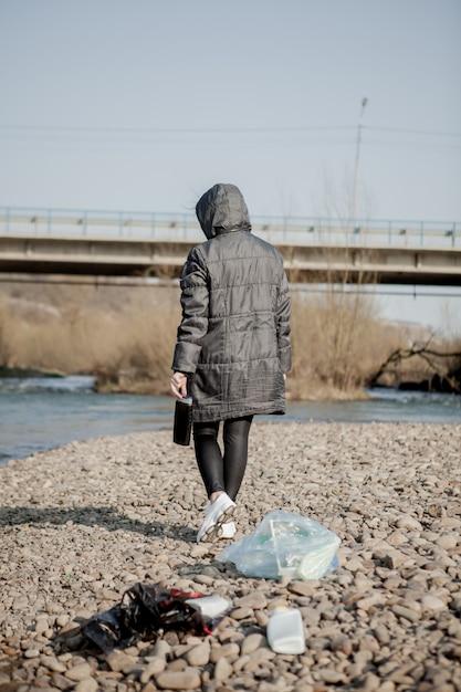 Junge frau, die plastikmüll vom strand sammelt und ihn für recycling in schwarze plastiktüten steckt. reinigungs- und recyclingkonzept. Premium Fotos