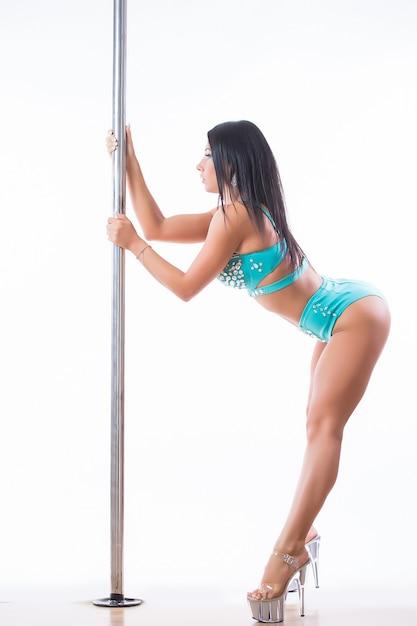 Junge frau, die pole dance fitness lokalisiert auf weißem hintergrund ausübt Kostenlose Fotos